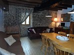 Spacious open plan living, stone walls, exposed beams and wood-burner.