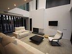 salón con chimenea, tv pantalla plana y sofás de diseño moderno