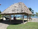 Hammocks and swing chairs under the palapa overlooking the beach
