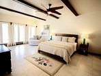Master bedroom with king bed, sitting area, doors to the pool/beach, ceiling fan, TV and A/C