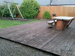 Enclosed area at rear of property with decking, picnic table, BBQ, swings, washing line.
