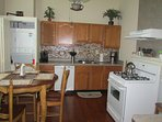 Kitchen featuring dining table for 4 or 6; gas stove; dishwasher; laundry; coffeemaker; toaster oven