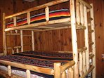 Bedroom with a full log bunk bed, queen on the bottom and a twin on top.