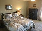Roomy bedroom with queen bed.