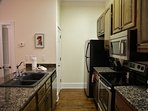 Fully equipped kitchen with stainless steel appliances. Pantry in front of fridge.