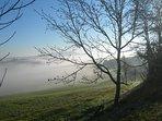 Au lever du jour, la brume d'un matin d'automne s'attarde sur les coteaux...