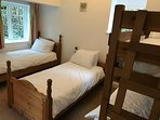 Bedroom Five at Riversdale Lodge - with two singles and one bunk bed. Also a flat screen tv with dvd