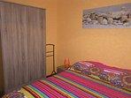 chambre avec lit 140x190 cm et son armoire.
