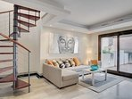 Stylish and comfortable living room with stairs leading to  the private swimming pool and terraces.