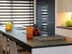 Moderne keuken met inductievuur, stoomoven, combi-oven, magnetron, koelkast, diepvries, vaatwas, enz