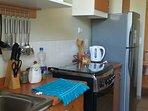 Cocina completamente equipada, cocina, refrigerador, hervidor, microondas y loza completa.