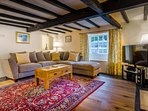 Cosy Tudor lounge with super comfy sofas, large flat screen TV and wood burning stove.