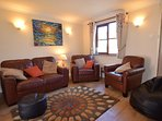 Comfortable living room with sofa, two armchairs and bean bag. Fresh, new laminate flooring.