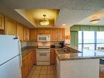 Fully equipped kitchen looks out onto comfortable dining and living space.