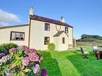 This traditional farmhouse has farmyard and outbuildings to the rear, but faces its own enclosed lawned gardens and...
