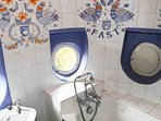 This fantastic turret bathroom with porthole style windows is the en-suite to the twin room
