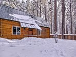 This cabin is surrounded by soaring pine trees.
