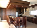 Spacious, modern kitchen with electric stove/oven, as well as a gas cooktop
