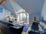 Modern open plan lounge, patio doors leading to balcony with sea views.
