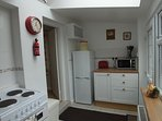 Kitchen with fridge freezer, microwave, cooker and washing machine . A step leads to the dining room