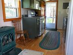 Glass-fronted gas stove keeps the cottage toasty on cool days.