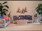 Living Room - Comfortable wicker and rattan furniture features fabrics with colorful island prints.
