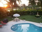 Spectacular summer sunset. View from upper porch overlooking back yard, pool, fountain and sun deck.