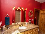 Master bath has a tiled, walk-in shower with bench and extra-wide vanity.