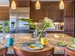 Sizeable kitchen island with bar seating and chic modern lighting.