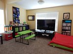 Kids' Play area in Game Room, including 58' TV with DVD player & library.