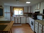 Fully stocked kitchen with all major appliances, cookware, dinnerware, and breakfast nook.