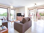 Spacious sun filled living area with two balconies, comfy new sofas and dining area