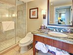 The guest bath offers a granite vanity and an elegant walk-in shower