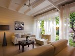 salon en cuir cosy sur la veranda ouvrant sur le frangipanier