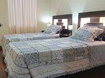 dormitorio con dos camas y vista a la calle, primer piso