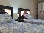 Dormitorio 2, con dos camas de plaza y media, ropero, dos mesas de noche, lamparas  y otros
