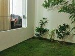 jardin interno y pequeño patio tipo terraza del departamento, con vista a la sala y comedor