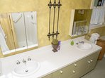 Lower bathroom with double sinks and shower / tub combinations