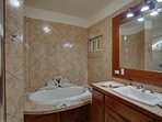 Master Bath with Jacuzzi tub and walk-in shower. Luxurious towels formed in lovely sculptures.
