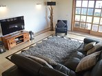 Living room with 55inch TV including Sky and UK tv package. Corner doors open to the garden.