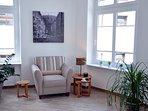 Gemütlicher Wohnraum. Zahlreiche hohe Fenster, welche mit hochwertigen Plissees ausgestattet sind.