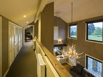 Double height living lounge ceilings from the mezzanine hallway above