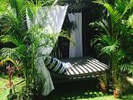 Romantic outdoir daybed in lush tropical gardens