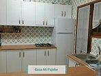 Halfopen keuken met grote koelkast en diepvriesvak, fornuis op gas.