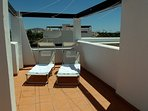 Rooftop terrace has large dining table, sunloungers, sun chairs and shade .