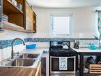 Well equipped kitchen with propane gas stove and concrete counters with beach glass. Unit B Upstairs