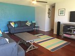 Living room in lively beachy colors, with 2 sofas, oversized chair, games, 50'HDTV, Wifi, BT Speaker