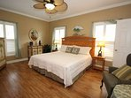 Spacious master bedroom with hardwood floor and new shutters