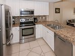 Kitchen with granite counters, stainless steel appliances and tile backsplash