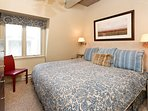 Master bedroom. Plush king size bed with down comforter and pillows, TV,